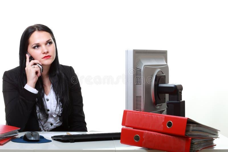 Telefono di conversazione moderno della donna di affari che si siede alla scrivania fotografie stock