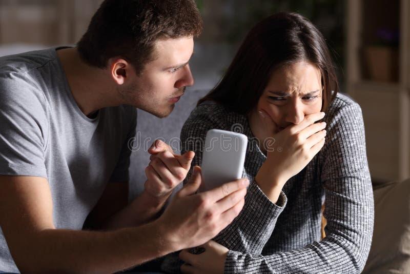 Telefono di manifestazione del ragazzo alla sua amica dell'imbroglione immagine stock