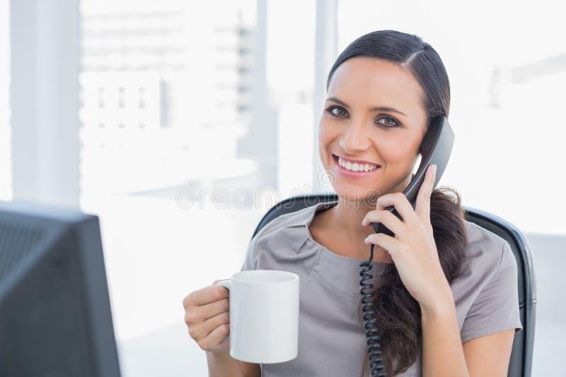 Telefono di risposta di segretario allegro e caffè bevente immagine stock libera da diritti