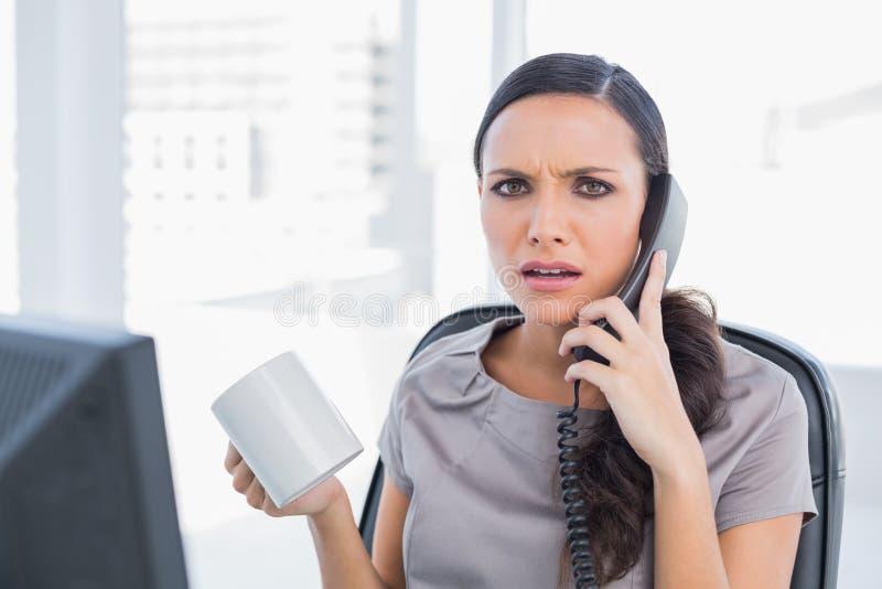 Telefono di risposta irritato di segretario immagine stock libera da diritti
