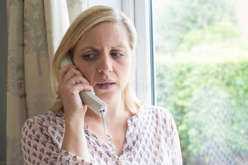 Telefono di risposta preoccupato della donna a casa fotografia stock libera da diritti