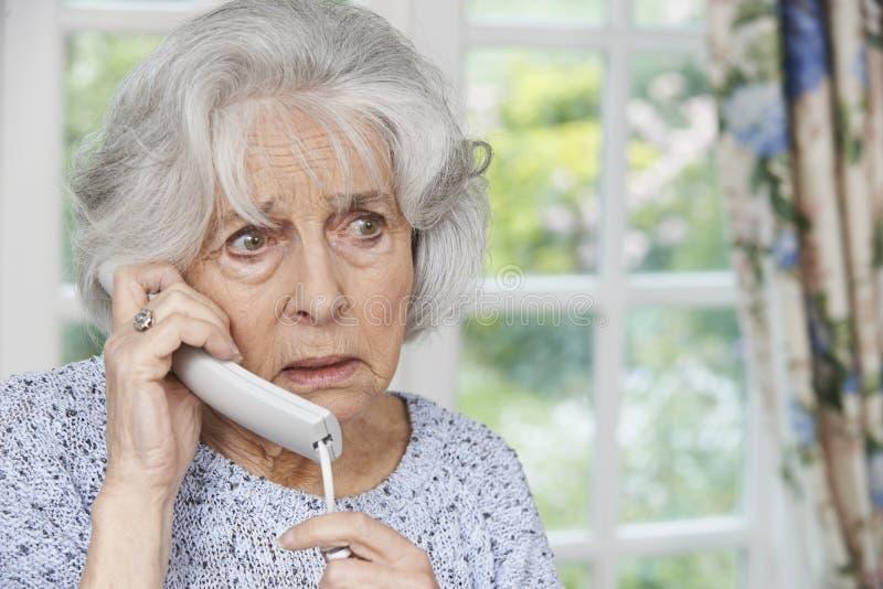 Telefono di risposta preoccupato della donna senior a casa immagini stock