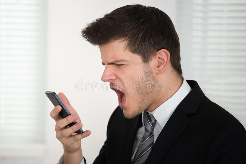 Telefono di Screaming On Smart dell'uomo d'affari fotografia stock libera da diritti