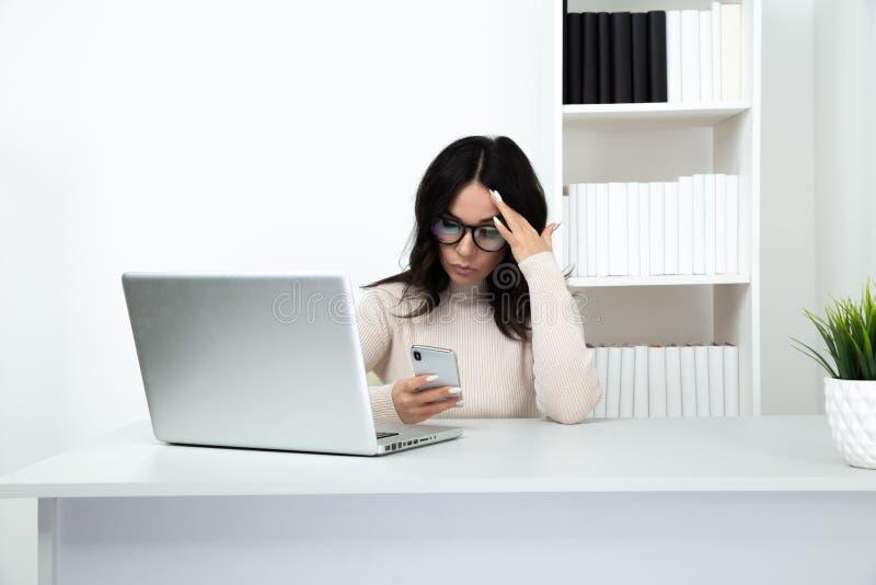 Telefono di sorveglianza infelice e frustrato di signora in ufficio che si siede davanti al computer fotografie stock libere da diritti