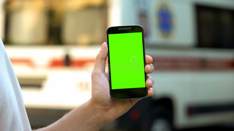 Telefono di tenuta paziente, ambulanza su fondo, sito con i consigli medici online fotografia stock libera da diritti