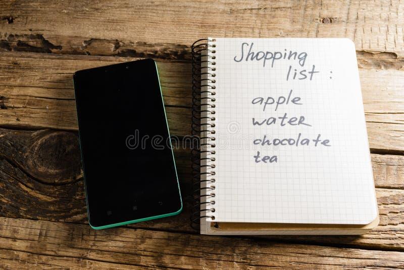 Telefono e diario notepads Una nota Lista di acquisto fotografia stock libera da diritti