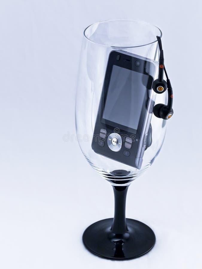 Telefono mobile in un bicchiere di vino. fotografia stock