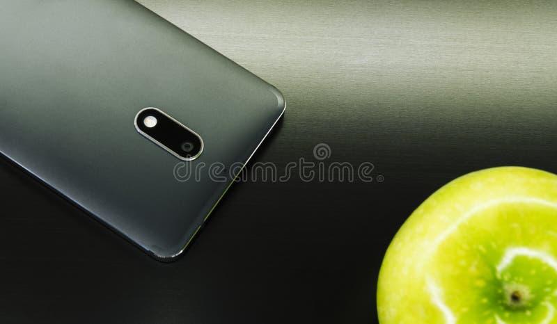 Telefono nero con una mela verde immagini stock