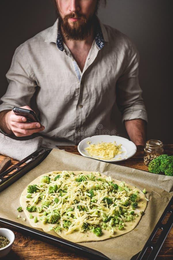 Telefono praticante il surfing dell'uomo mentre cucinando immagine stock libera da diritti
