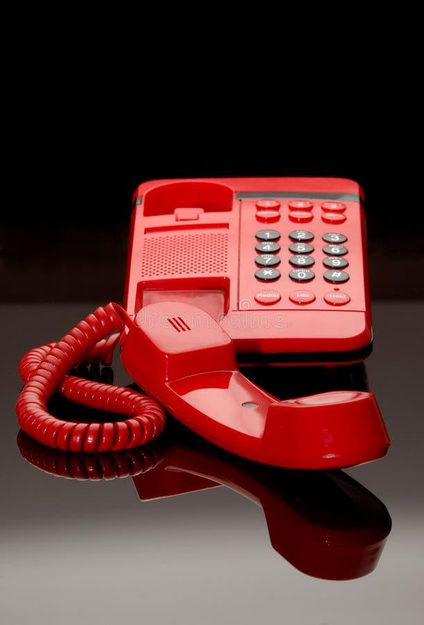 Telefono rosso su vetro nero fotografia stock