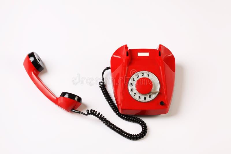 Telefono rotatorio rosso fuori dal gancio su fondo bianco fotografia stock libera da diritti