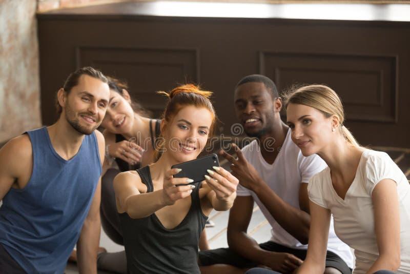 Telefono sportivo attraente della tenuta della donna che prende il selfie del gruppo al tra fotografia stock