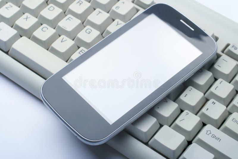 Telefono sulla tastiera di computer immagine stock libera da diritti