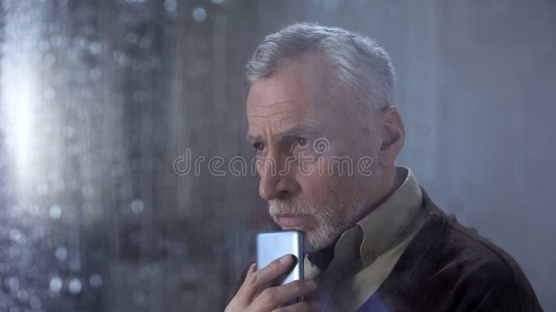 Telefono turbato della tenuta dell'uomo senior, chiamata aspettante dai bambini, gocce di pioggia fotografia stock libera da diritti