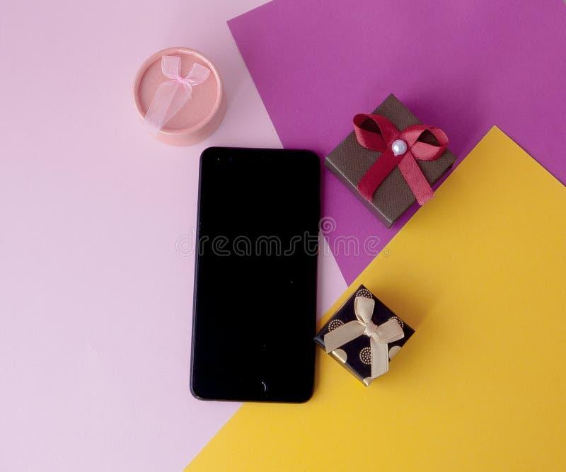 Telefonskärm och gåvor på kulör bakgrund Minsta begrepp Lekmanna- lägenhet Top beskådar Online-befordringar och rabatter gåvaferi fotografering för bildbyråer