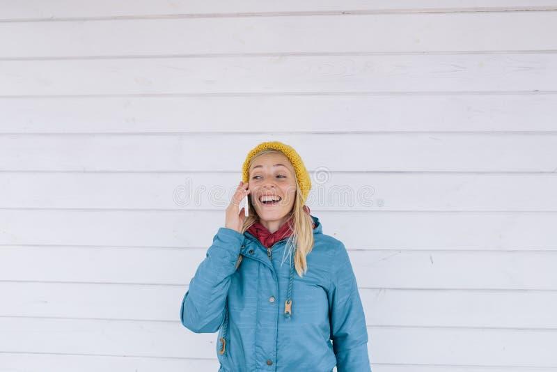 telefonu ja target1387_0_ target1388_0_ kobiety potomstwa kobieta w kolorze żółtym dział kapelusz i niebieską marynarkę używać te obraz royalty free
