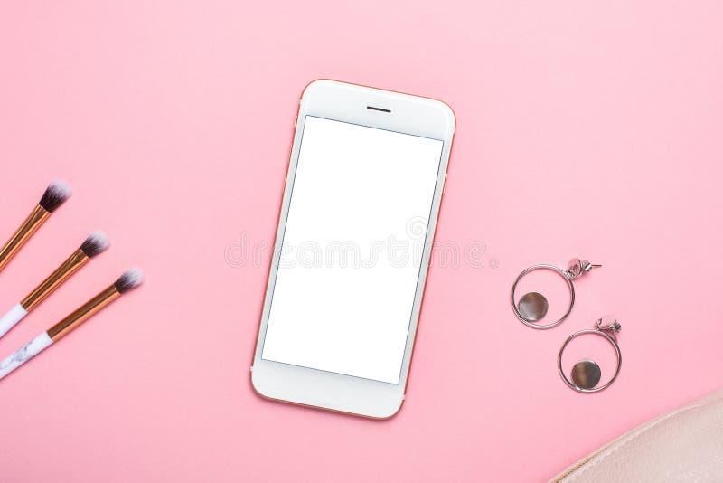 Telefonu komórkowego egzamin próbny z w górę makeup muśnięć i kolczyki na różowym pastelu stole w mieszkaniu kłaść styl Kobiety p zdjęcia stock