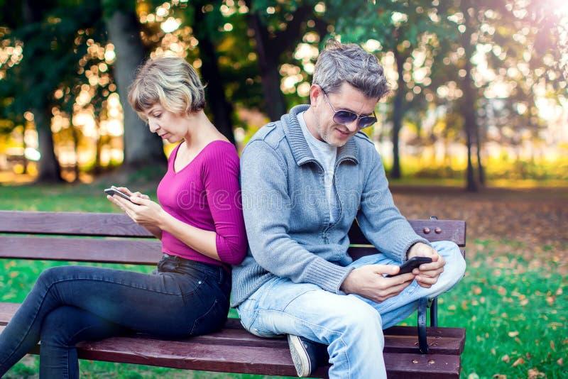 Telefonu komórkowego nałogu pojęcie - dobiera się patrzeć ich wiszącą ozdobę obraz royalty free