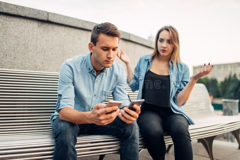 Telefonu nałogowa mężczyzna ignoruje kobiety z dwa gadżetami zdjęcia royalty free