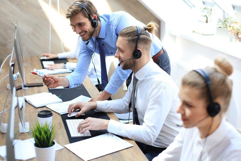Telefonu operator pracuje przy centrum telefoniczne ksyka biurowym pomaga koleg? obraz royalty free