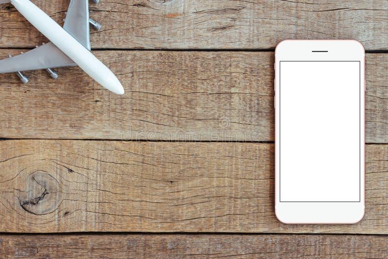 Telefoon en vliegtuigstuk speelgoed op houten van het bedrijfs lijstvervoer concept stock foto's