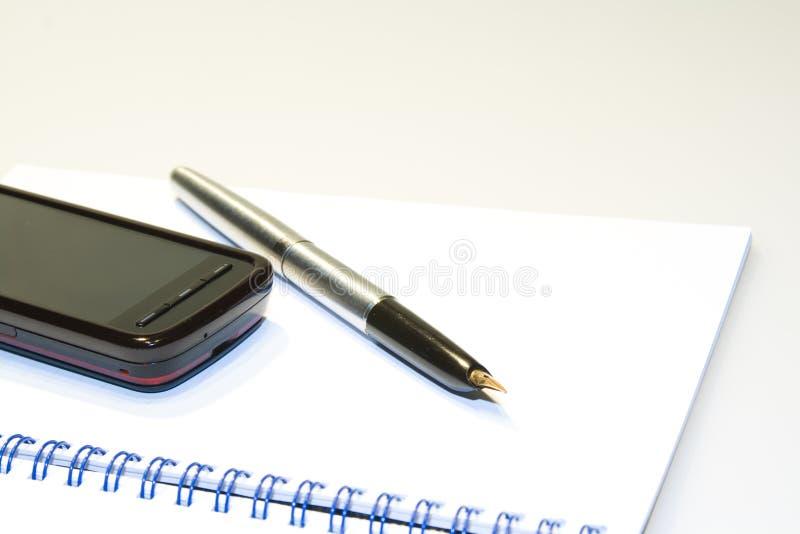 Telefoon op notitieboekje stock foto
