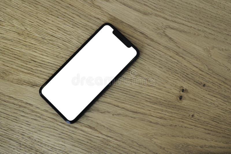 Telefoon ter beschikking op de achtergrond van bomen, park, tuin Lay-out voor de toepassing Telefoon met het wit scherm Het zwart stock afbeeldingen