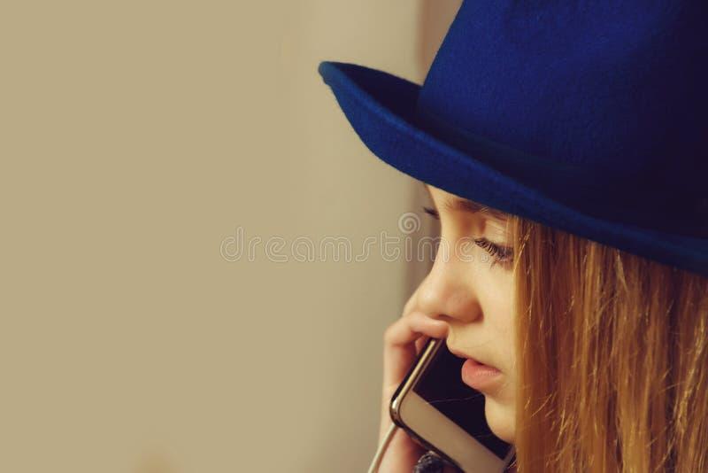 telefoongesprek van vrouw in hoed die op mobiele telefoon spreken stock afbeelding