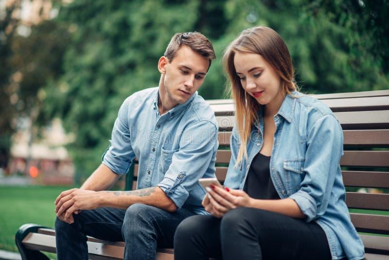 Telefoonverslaving, jong paar op de bank in park stock foto