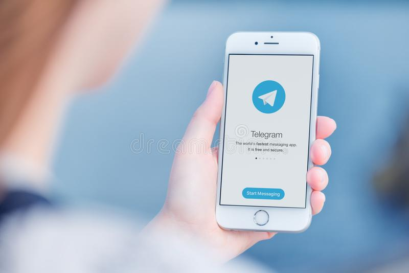 Telegram messenger on Apple iPhone in woman hands over the shoulder view stock photo