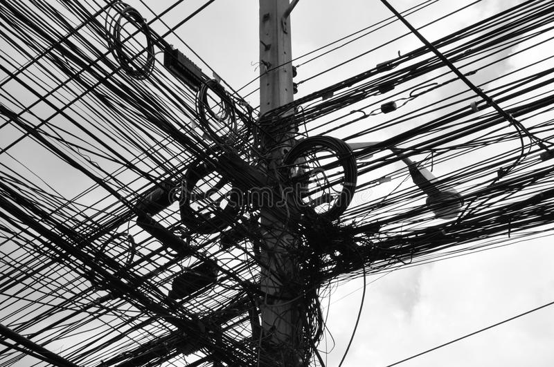 Telegraph pole with many wires. Black & white image of a telegraph pole with a chaotic mass of many wires royalty free stock photo