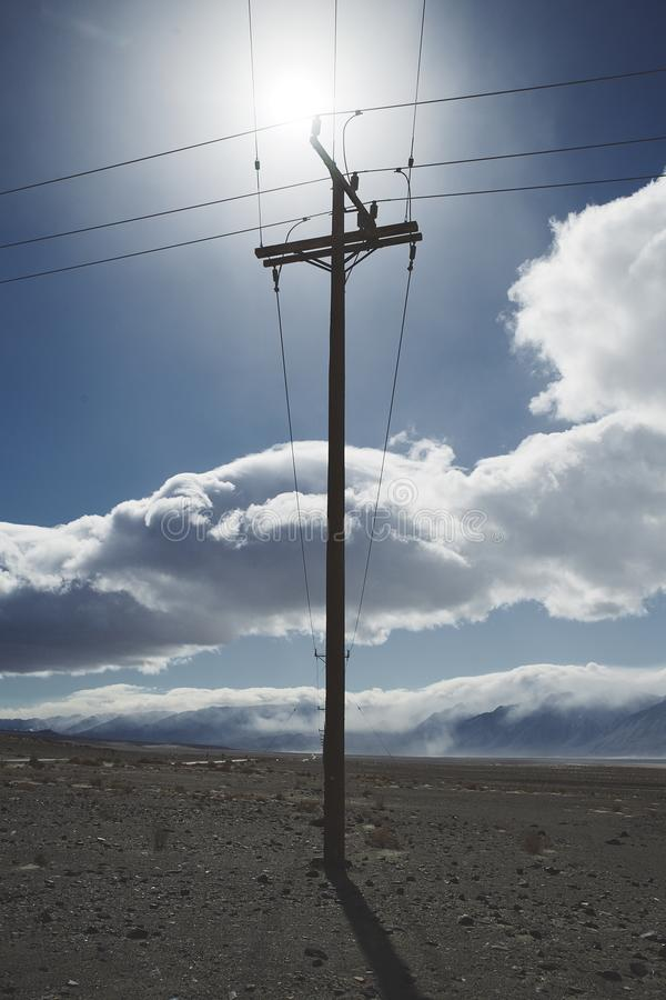 Telegraph utility pole silhouette in desert. Telegraph utility pole silhouetted by bright sun directly behind. Bright blue sky with clouds. rocky desert royalty free stock image