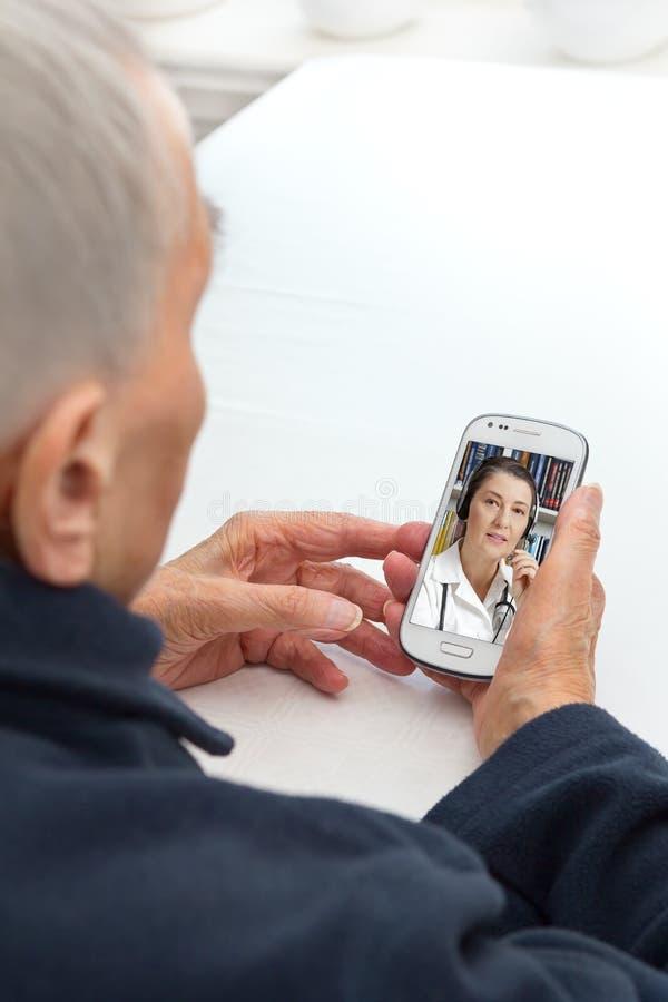Telehealth da telemedicina do smartphone da pessoa idosa foto de stock