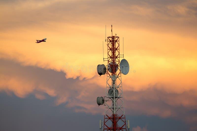 Telekommunikation signalisieren Turm im Sonnenuntergang und Flugzeug fliegt durch stockfotografie