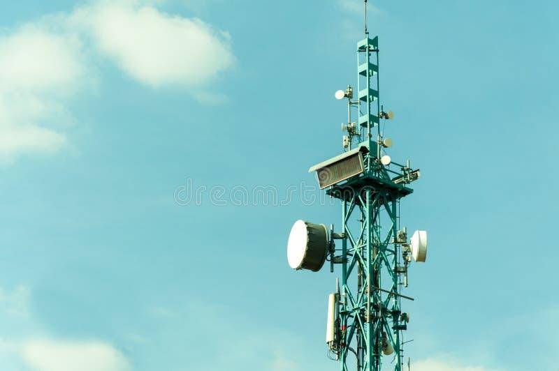Telekommunikationantenner som är utomhus- på den högväxta metallpolkonstruktionen med skärm för digital klocka och bakgrundsslut  royaltyfri foto