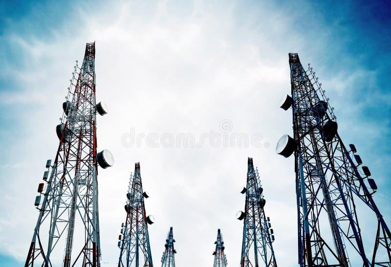 Telekommunikationen står högt med TVantenner och den satellit- maträtten på klar blå himmel fotografering för bildbyråer