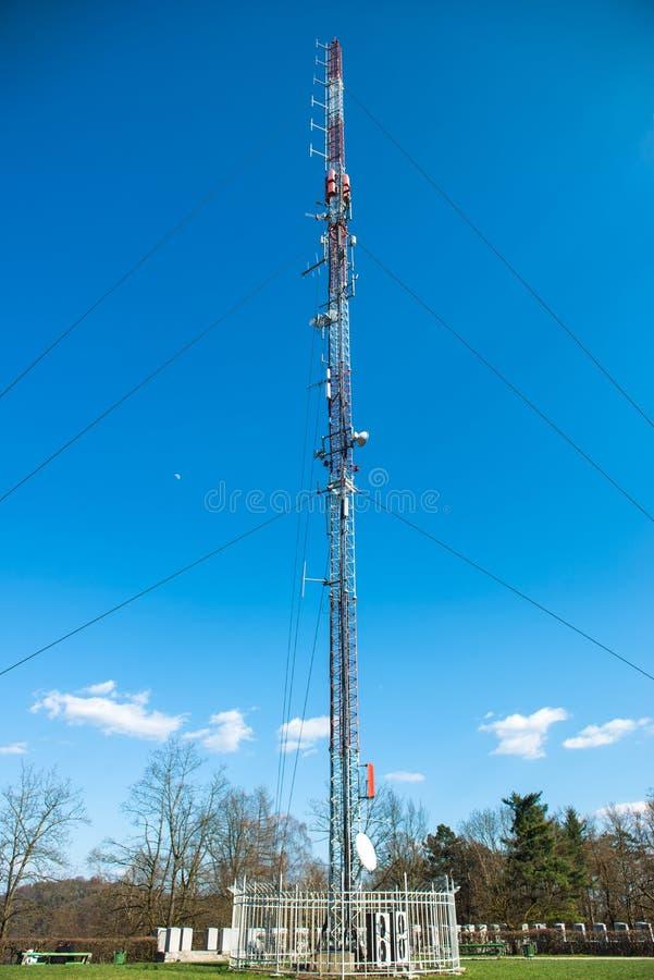 Telekommunikationradiotornet i staden parkerar royaltyfria bilder