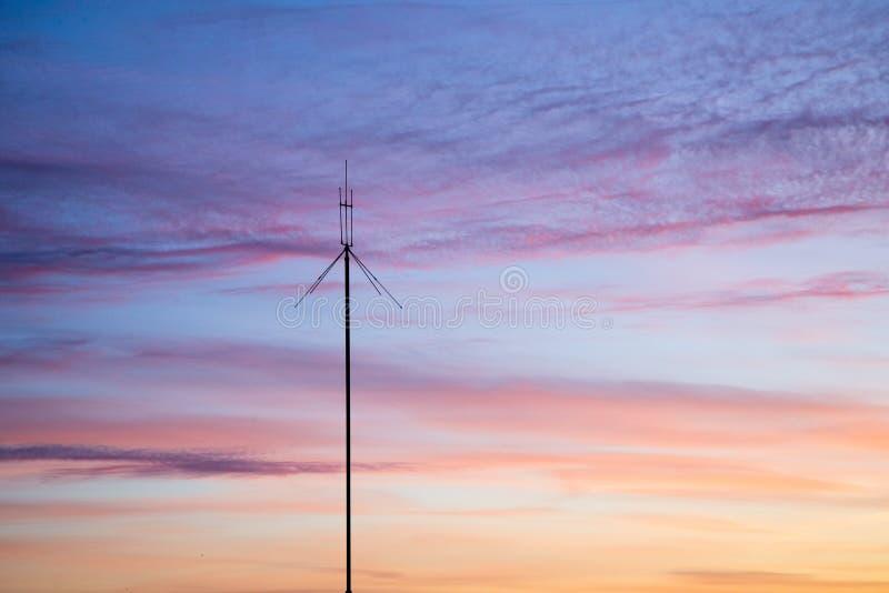 Telekommunikationsmaste von Fernsehantennen gegen einen Sonnenuntergang stockfotografie