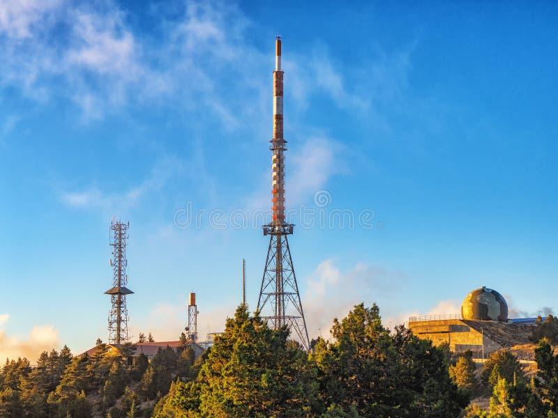 Telekomunikacja góruje z TV anteną satelitarną w zmierzchu i antenami obrazy stock
