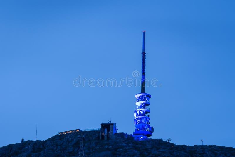 Telekomunikacji wierza zaświecał w górę błękit colorised światła z przeciw niebieskiemu niebu zdjęcie stock