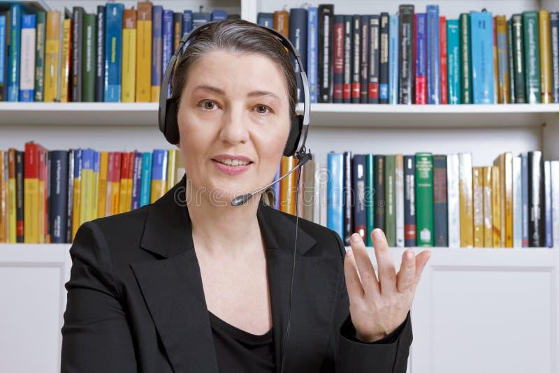 Telelearning för böcker för kvinnahörlurar med mikrofonkontor arkivbilder