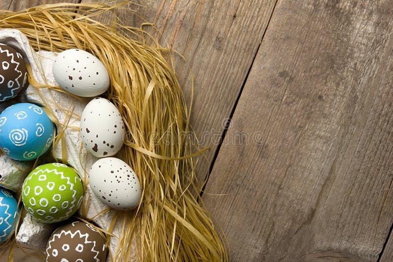 Telemóvel amarelo Ovos da páscoa pintados em um ninho em um fundo de madeira natural com espaço da cópia para felicitações foto de stock