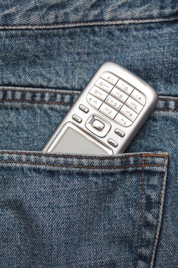 Telemóvel em um bolso das calças de brim foto de stock royalty free