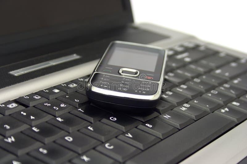Telemóvel em um teclado do caderno imagem de stock