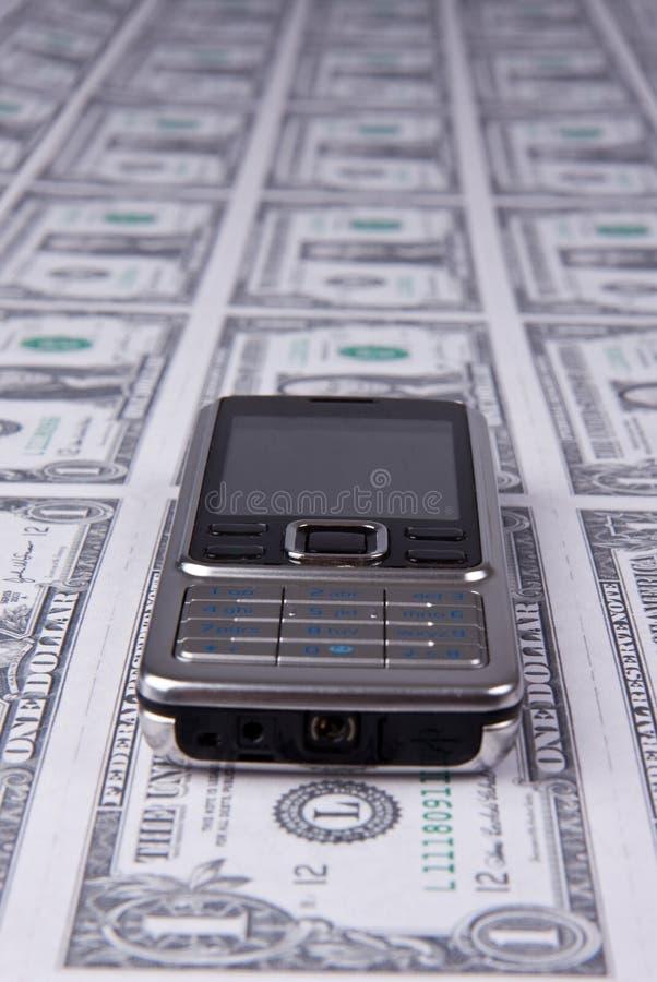 Telemóvel no fundo do dinheiro imagem de stock royalty free