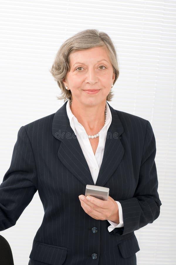 Telemóvel sênior da preensão do sorriso da mulher de negócios fotos de stock royalty free