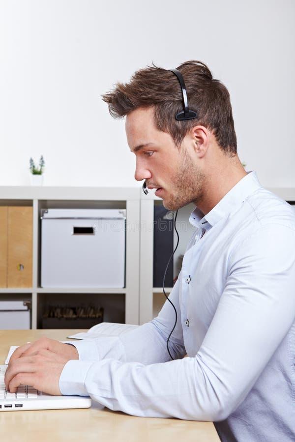 Telemarketing employee with headset royalty free stock photo