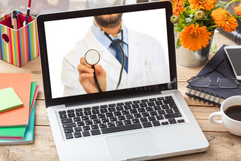 Doctor GP on a computer screen, office desk background. Telemedicine concept. Doctor GP on a computer screen, office desk background stock photography