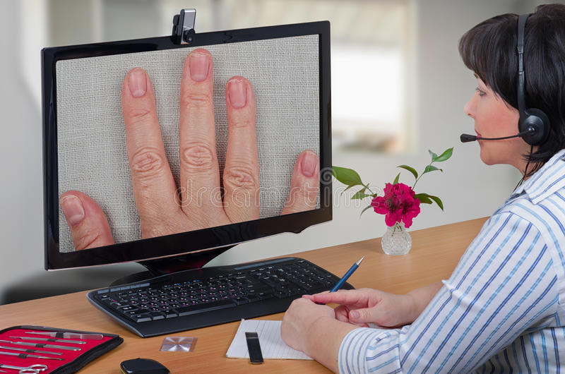 Telemedicine dermatologist looking fingernails. Telemedicine female dermatologist in headset looks at peeling off nails layers of female patient on monitor with royalty free stock image