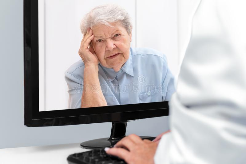 Telemedicine and e-health with a doctor and a elderly woman with afflictions royalty free stock images